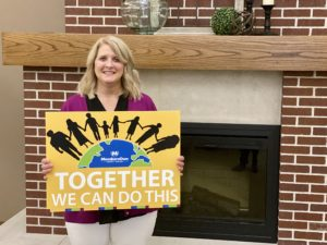 Linda Carter, President of MembersOwn Credit Union, holding a sign that says together we can do this