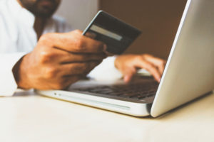 Debit Card Fraud alert: Person holding a credit card while typing on a laptop computer.