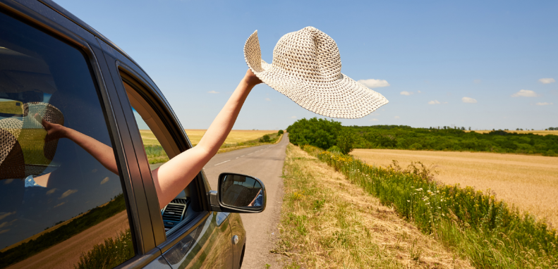 Woman holding her hat out of an open car window while driving on a Nebraska road.
